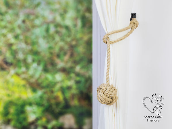 A beige rope curtain tieback with a monkey fist knot on a white curtain.