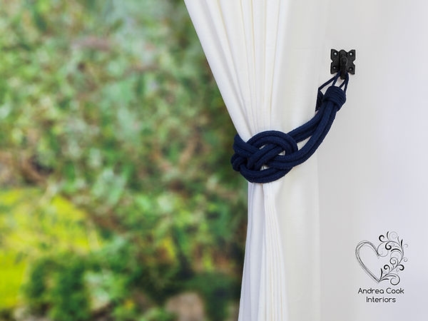 A navy blue double carrick knot curtain tieback on a white curtain
