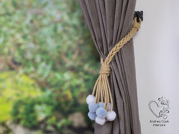 A beige braided curtain tieback with grey and white pom poms for nurseries.
