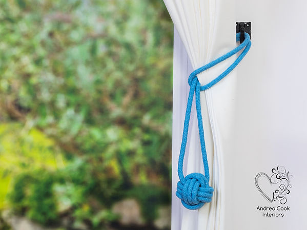 Light blue curtain tiebacks with a monkey fist knot on white curtains