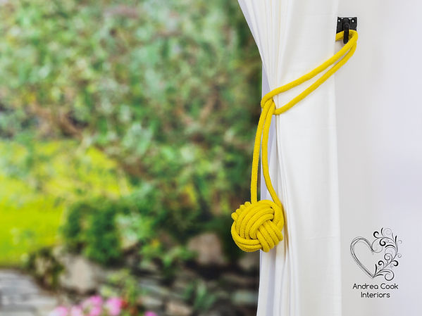 Yellow curtain tie back with a monkey fist knot on a white curtain.