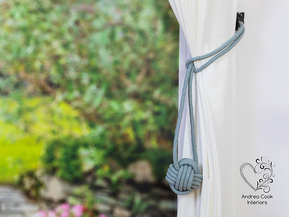 light grey curtain tiebacks with a monkey fist knot on white curtains