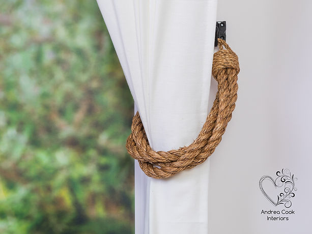 Twisted chunky manila rope curtain tieback for naurical decor. On a white curtain.