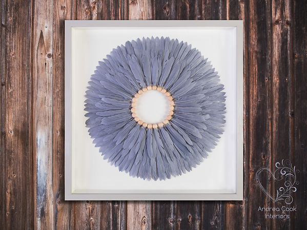 Handmade feather circle artwork using grey feathers, insude a box frame that has been painted grey and white