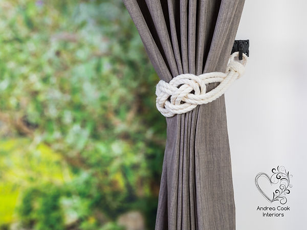 Handmade white curtain tieback made with a double carrick knot, on a grey curtain.