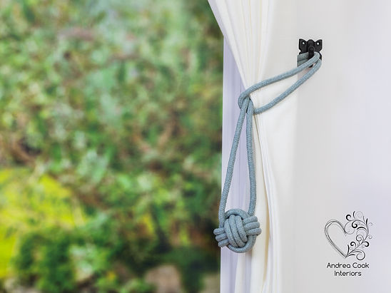 A light grey curtain monkey fist tieback made with cotton cord and on a white curtain.