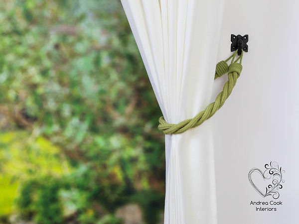 Green tiwsted cotton cord twisted curtain holdbacks on a white curtain