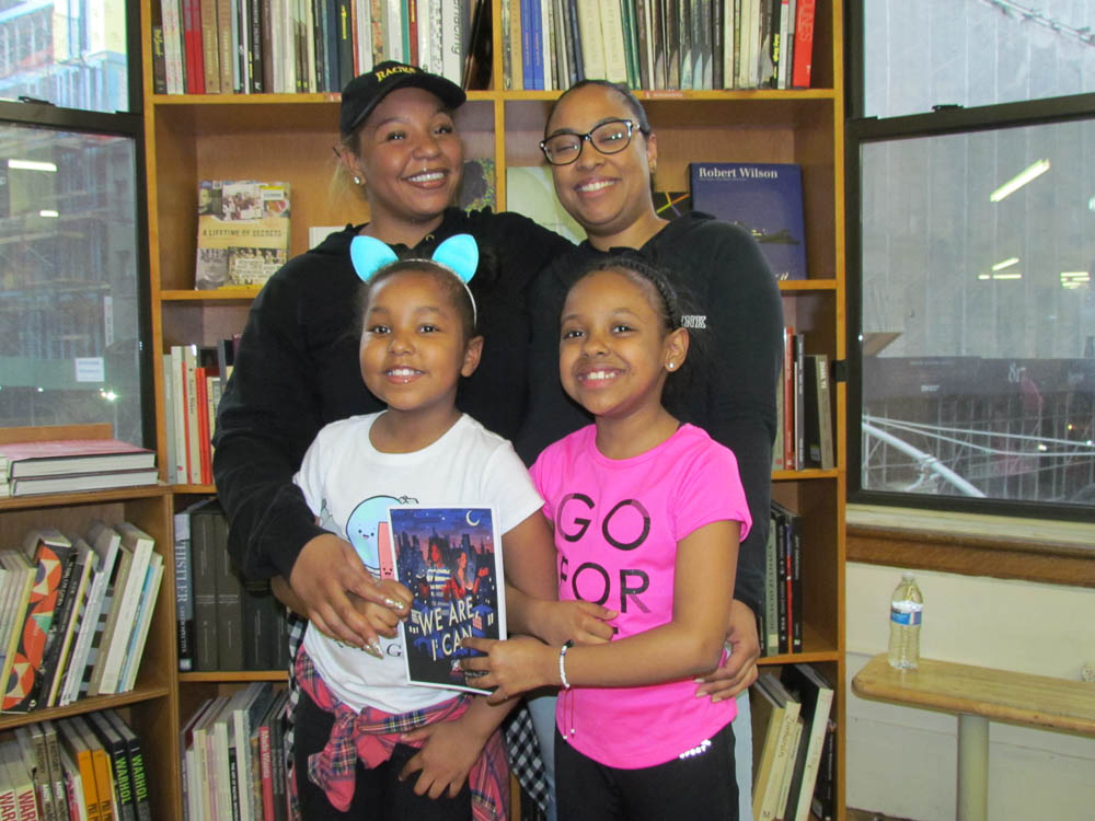 """Jaylene and Ameil posing with their moms and a special edition of """"We Are, I Can"""""""