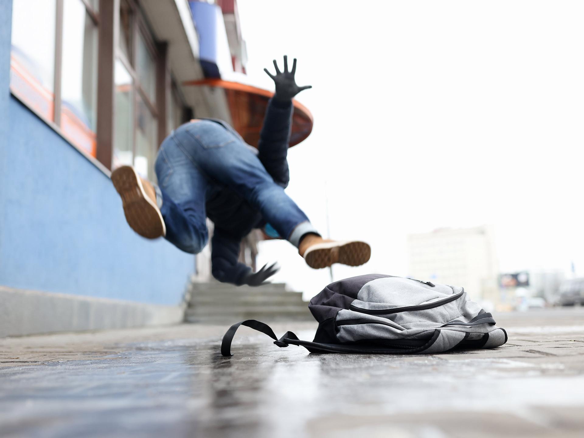 man tripping on the sidewalk