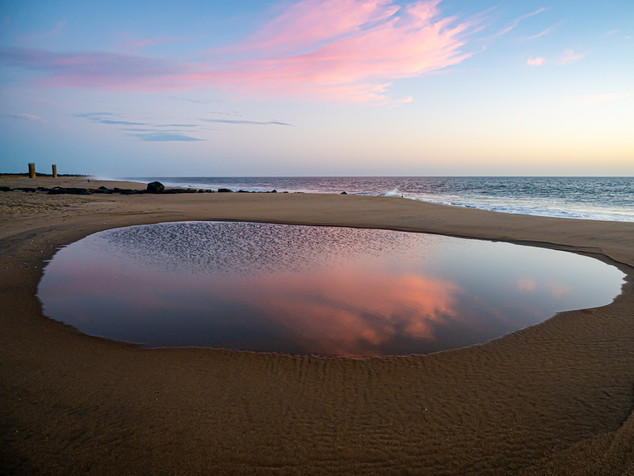 tide pool with pink cloud reflections