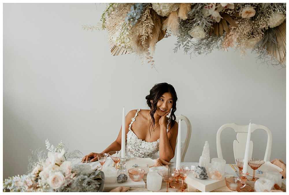 bride in flower dress sitting down at table
