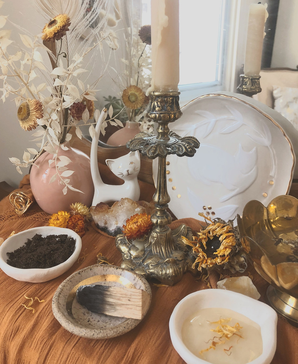 gold and yellow full moon altar with beeswax candle in antique brass, honey and calendula for offering, a bouquet of flowers, and the 4 elements