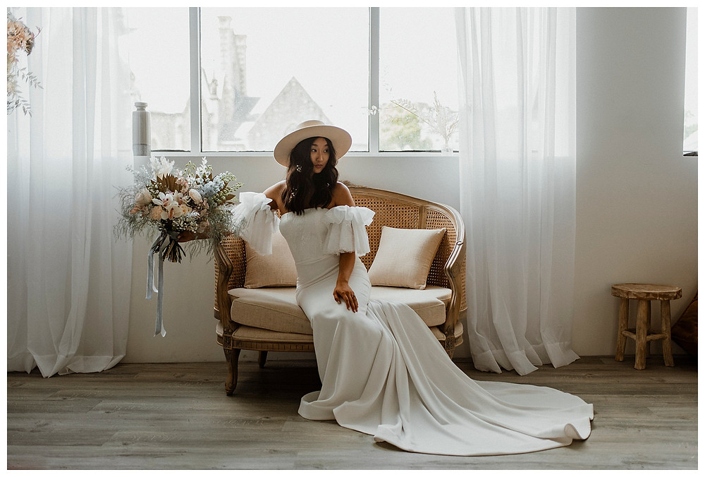 bride in hat on vintage couch with flowers
