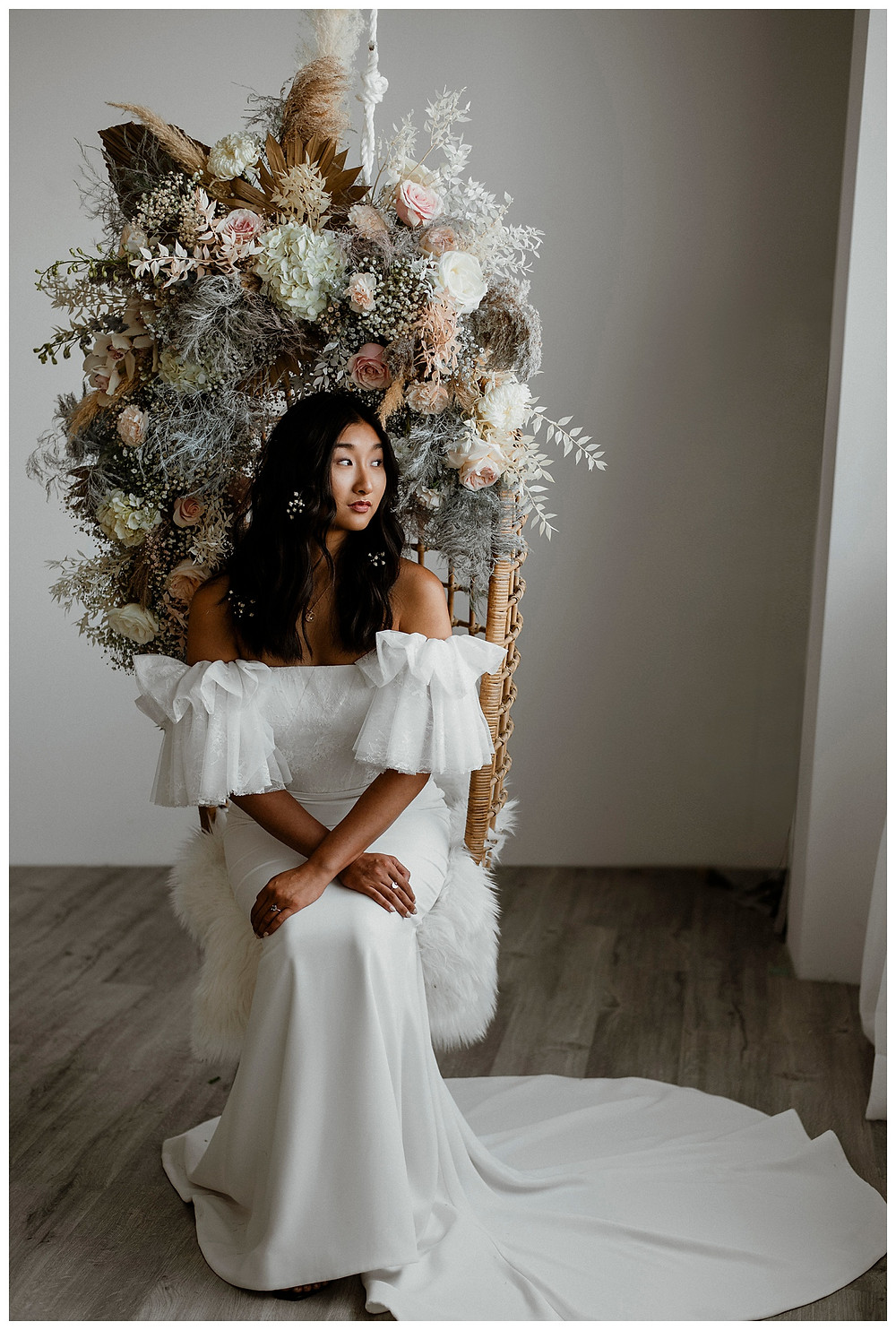 bride in hanging chair and floral installation