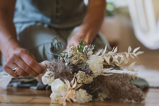 woman hand-tying dried neutral bouquet of flowers