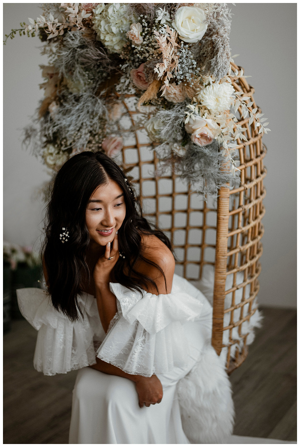 bride sits in hanging rattan chair