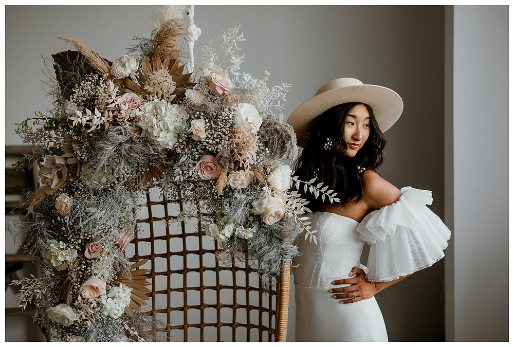 modern bohemian bride in hat with floral installation