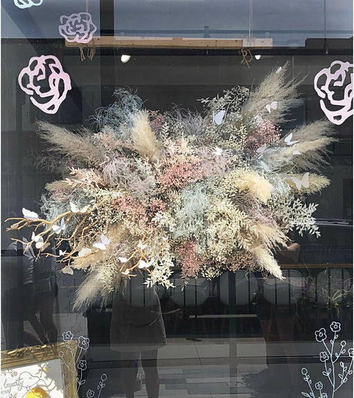 dried fluffy pastel ethereal floral cloud installation with butterflies hanging in shop window
