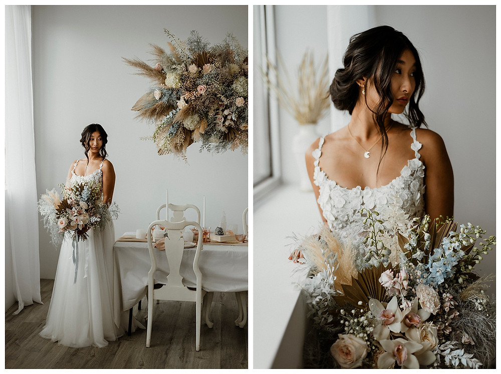 bohemian bride standing by table with dried floral cloud and bouquet