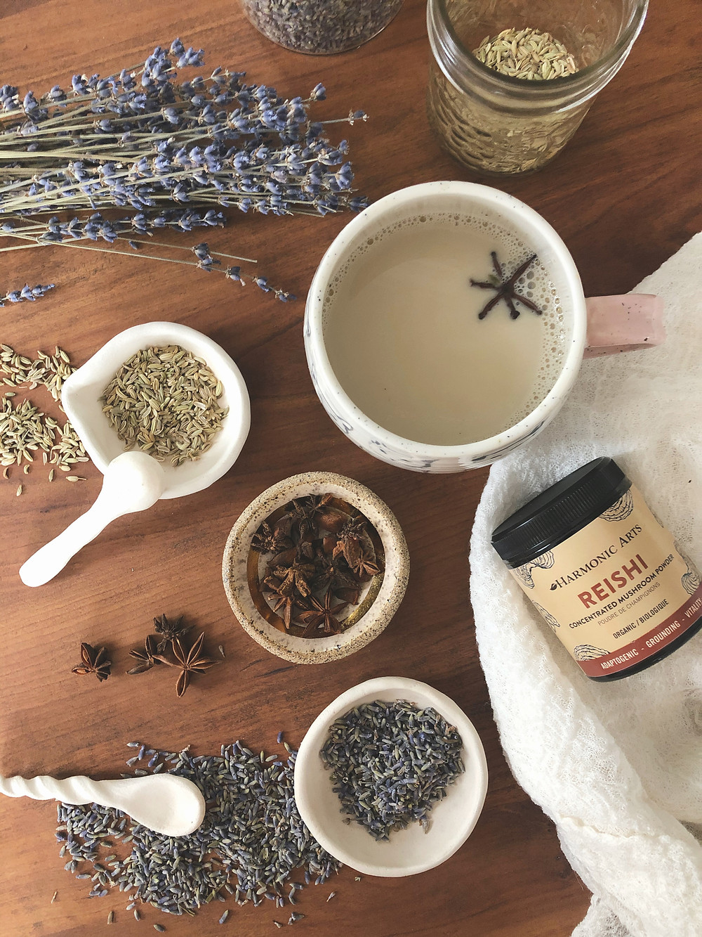harmonic arts reishi powder, loose fennel, lavender and star anise on table with oat milk infused with herbs for mercury retrograde