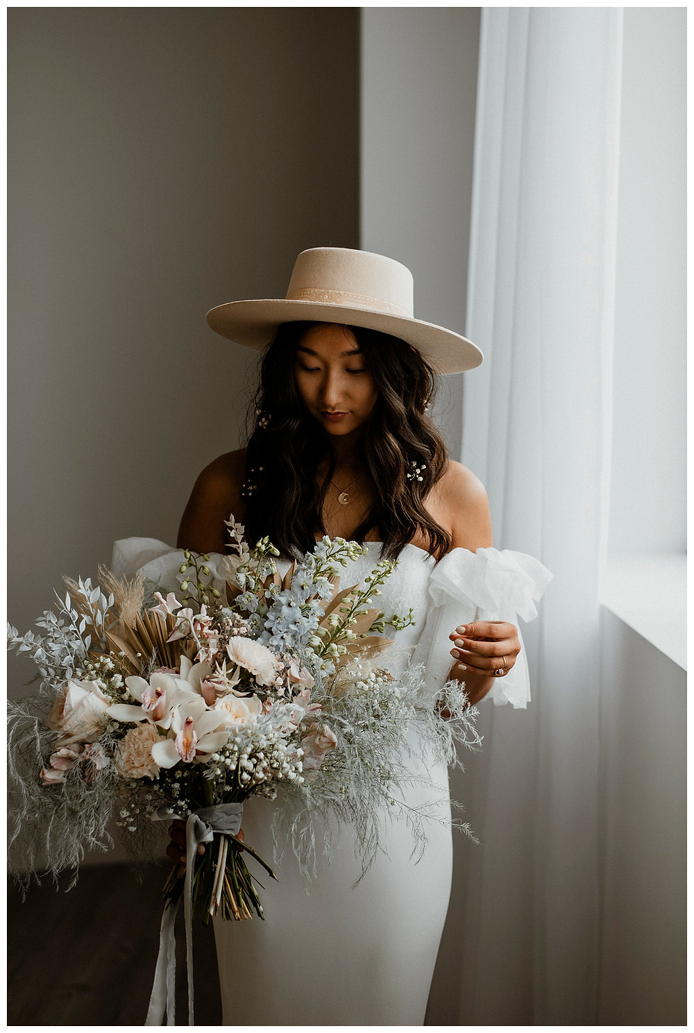 bride in wide brim hat with cloud-like bouquet