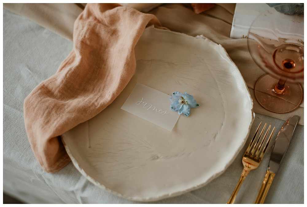 handmade white ceramic dinner plate with gold cutlery, blush linen napkins on tablescape
