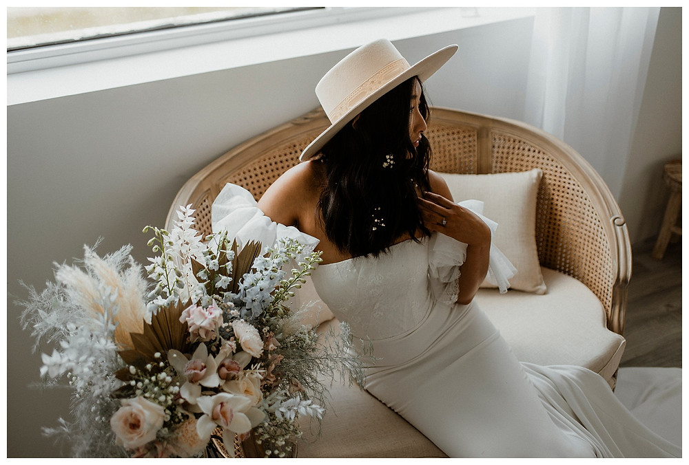 bohemian bride on vintage settee holding bouquet of flowers