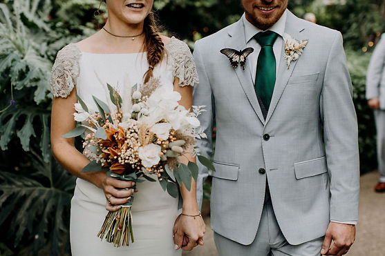 bohemian bride and groom holding hands and dried white rust and green bouquet with butterflies
