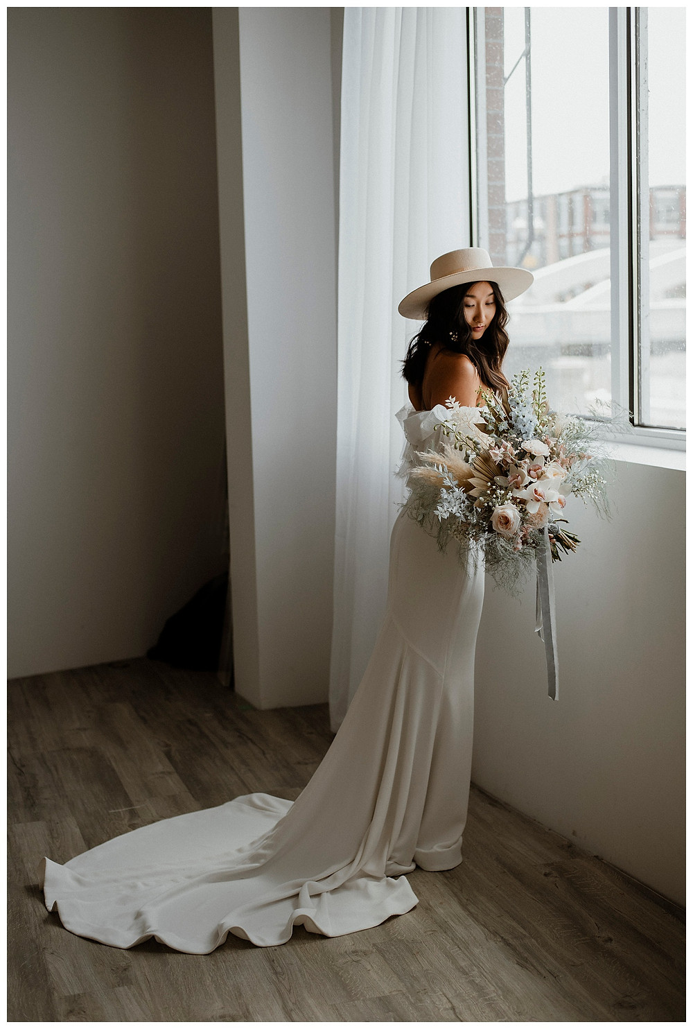 bride in cream hat stands by window with fluffy pastel bouquet