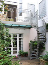 A fantastic example of our standard spiral staircase design. With cast iron balusters, cast treads and a hand bent steel handrail this is a wonderful architectural addition to the exterior of the property. We also installed a cast iron balustrade and steel frame for the glass balcony.