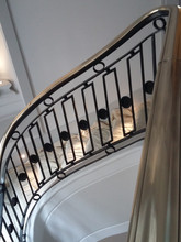 Solid brass handrail with fabricated steel and cast iron baluster pattern.