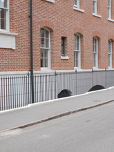 Core drilled and installed mild steel railings with our bespoke cast iron finials made in the UK.