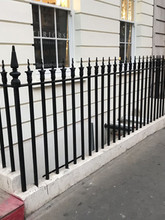 Bespoke cast iron finials with mild steel railings individually core drilled and installed finished in black. Square corner posts with replicated finial pattern to match.