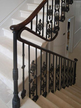 A traditional cast iron balustrade and newel post with wooden handrail adoring the top.