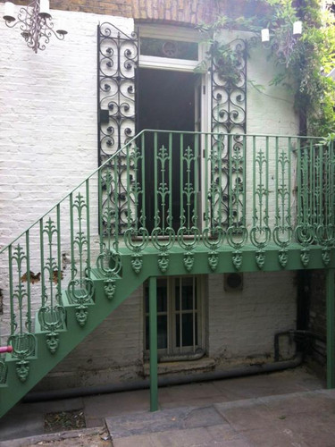 Cast iron external staircase finished in green. A lovely Victorian cast pattern used here for these ornate cast balusters.