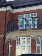Intricate cast iron balcony balustrade panels fully installed.