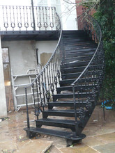 Curved cast iron staircase – incorporating cast iron balusters, cast iron treads and a hand bent steel handrail. Finished in the traditional gloss black.