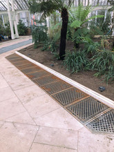 Cast iron floor grilles in bare metal installed at Kew Gardens.