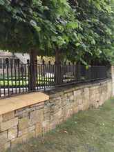 Fabricated mild steel wall top railing panels with cast iron finials.