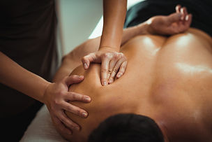Physiotherapist massaging male patient w