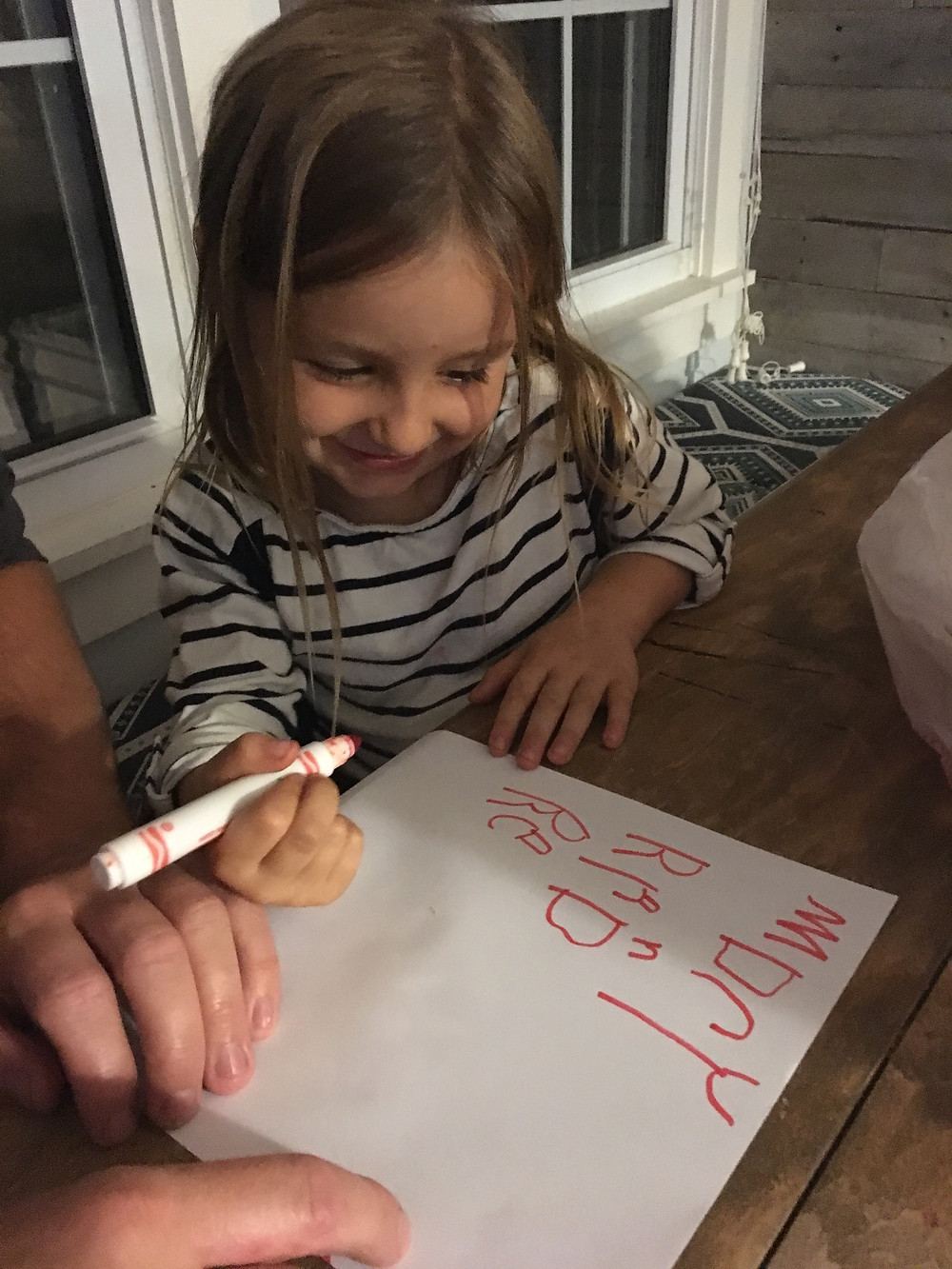Our daughter, one of our Savvy Apple kids, writing the names of her friends.