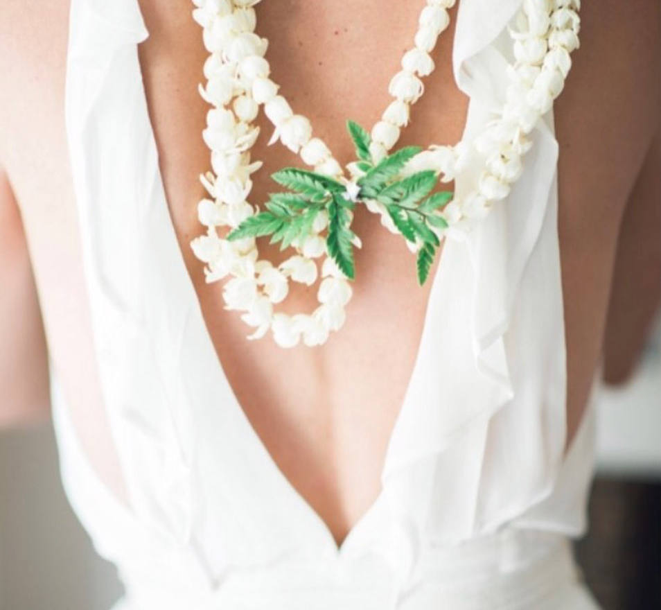 Brides back with white lei and garland