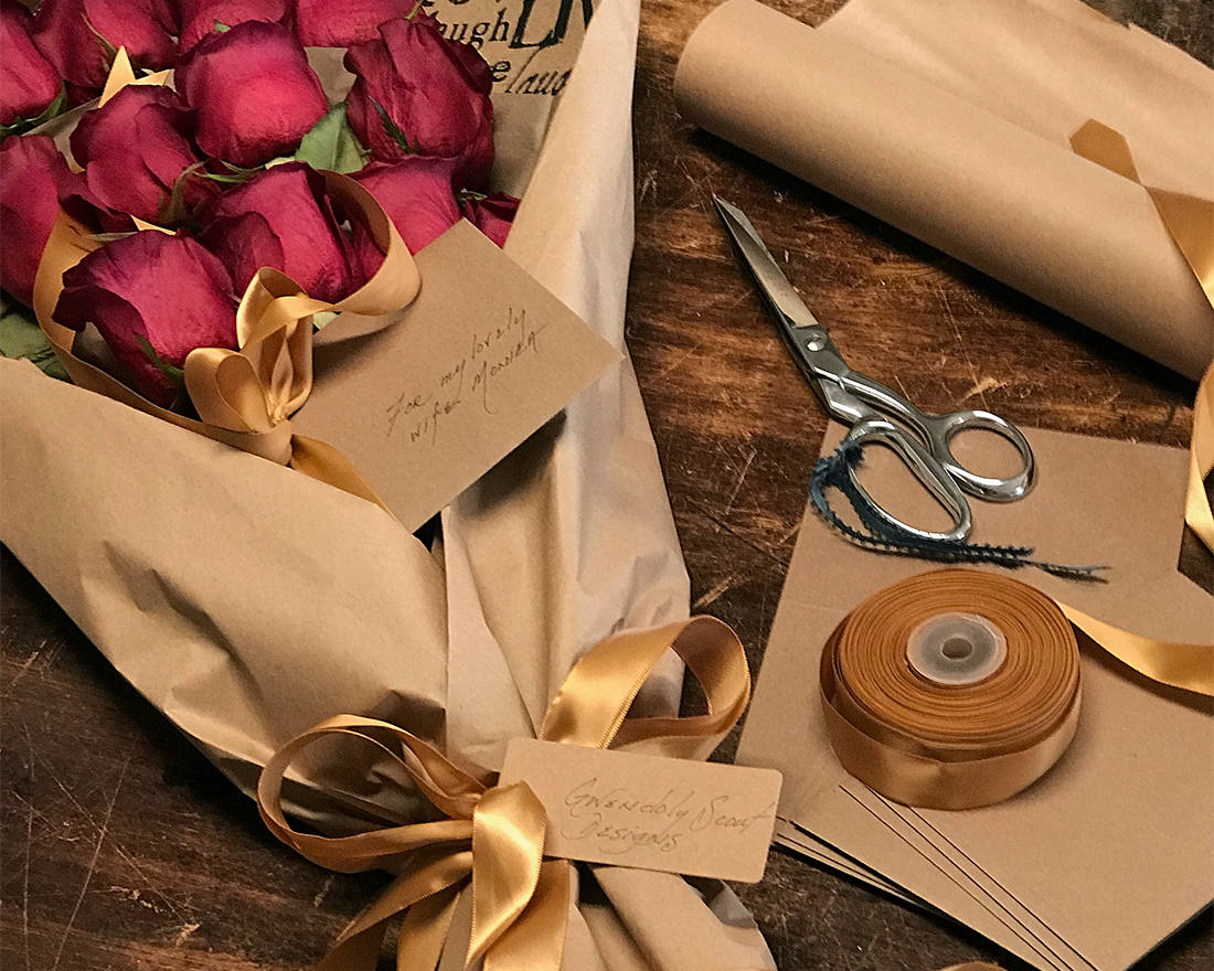 Roses wrapped in brown paper with gold ribbon