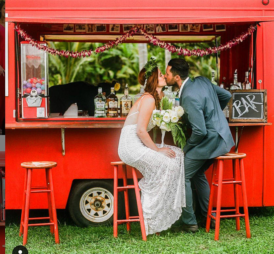 Bride and groom embracing at flower truck on stools with white gl