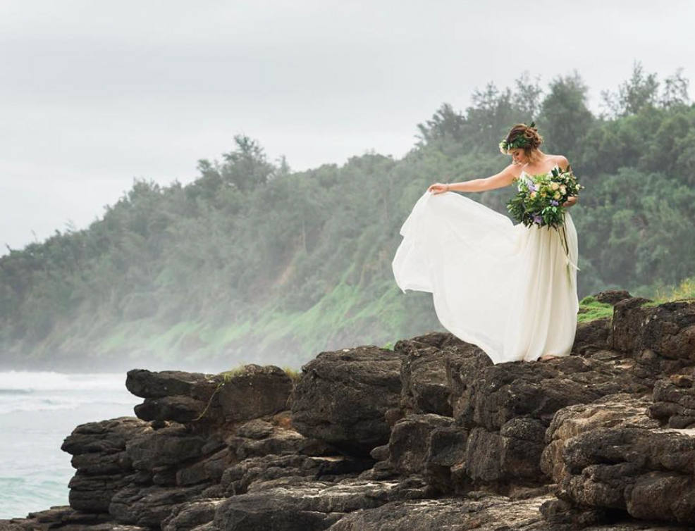 Bride on kauaii beach with flowing dress and floral arrangement