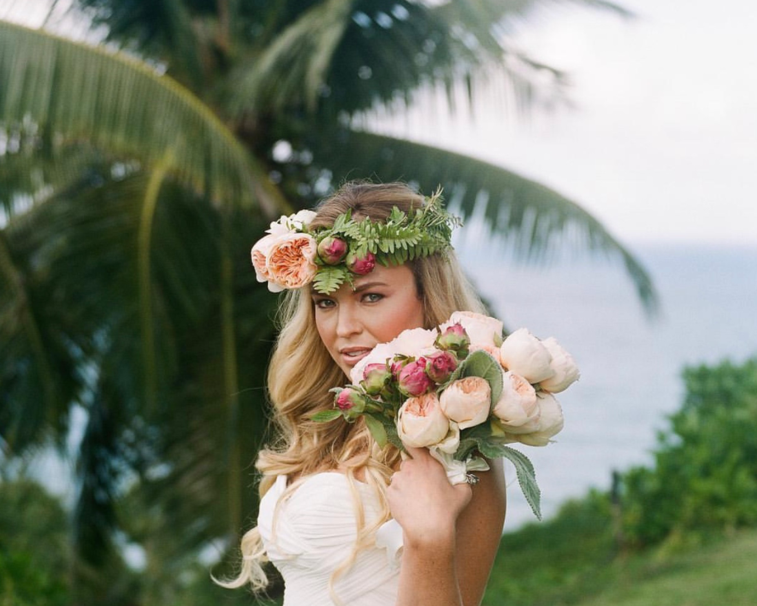Beautiful blond bride with pink roses and crown against Kauaii palm trees and ocean