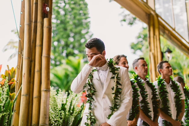 Groom and groomsmen with leis and garlands waiting for bride