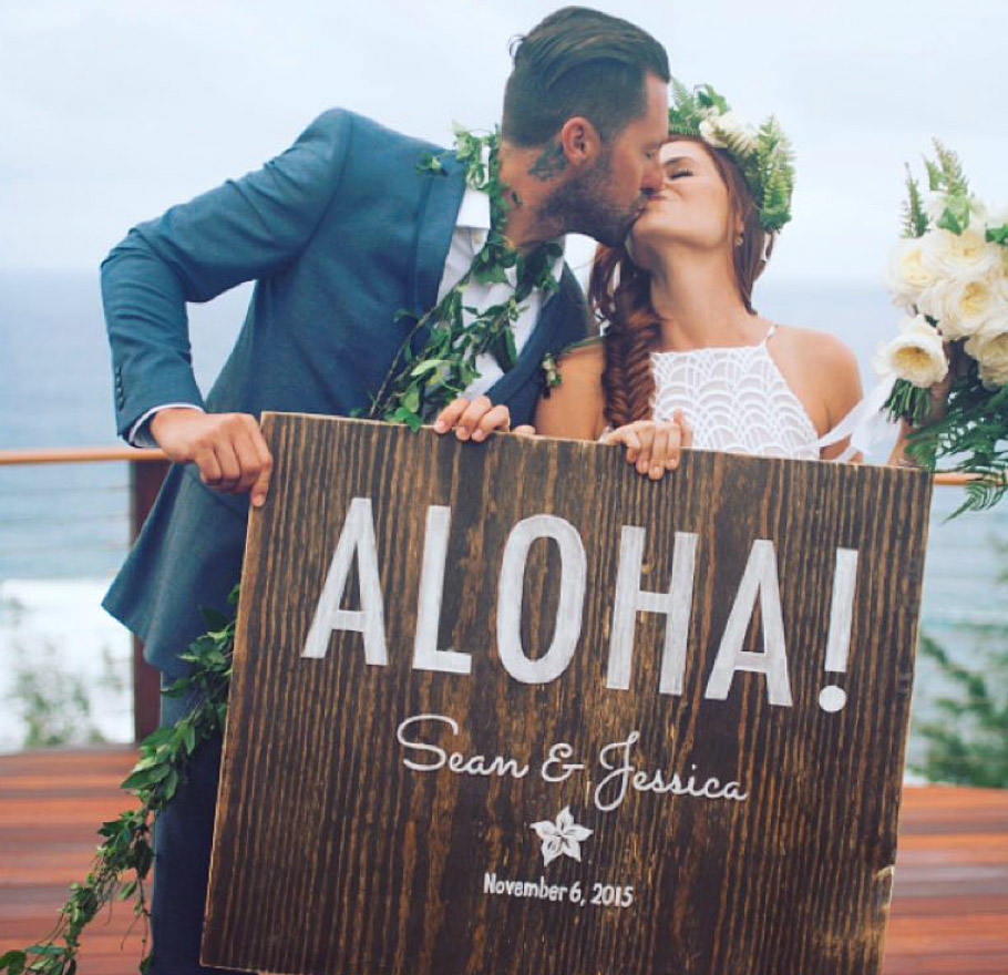 Married couple holding and ALOHA sign with lei or garland