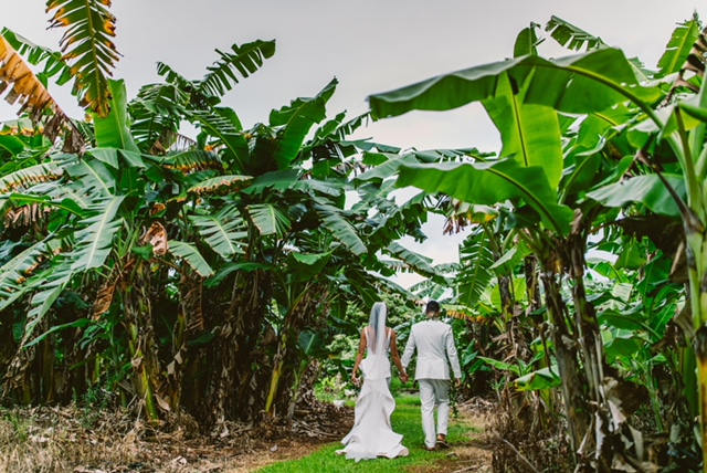 Bride and groom walking hand in hand through the kauaii floral