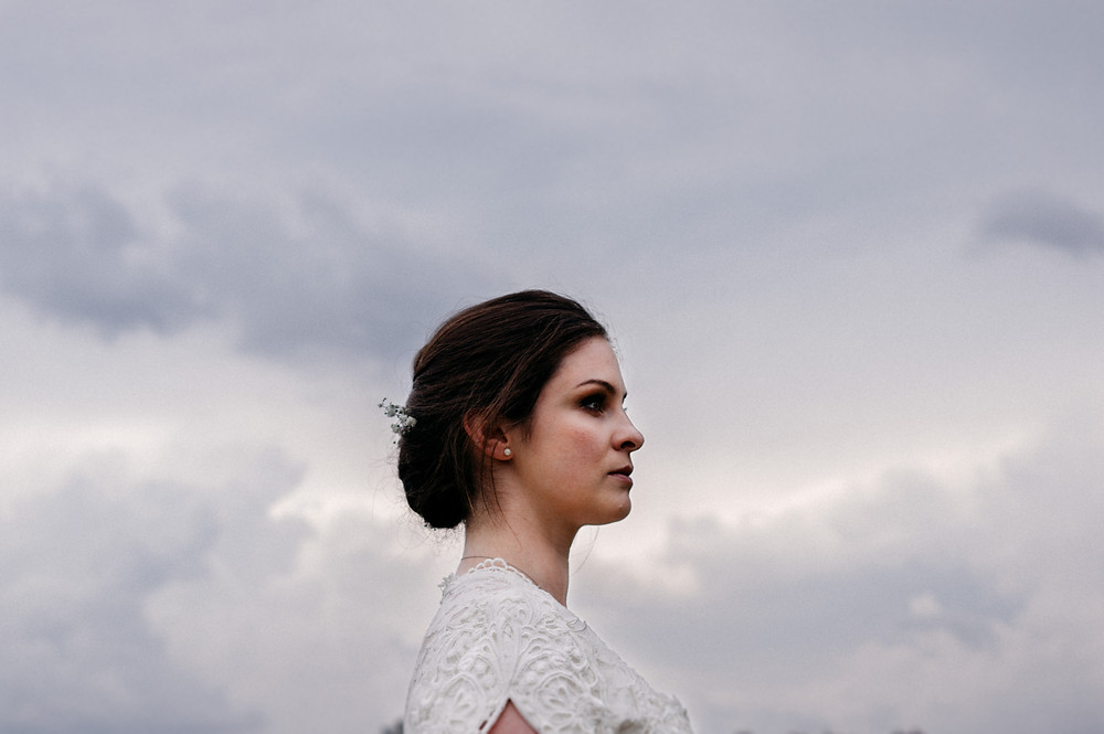 woman in a wedding dress with stormy sky